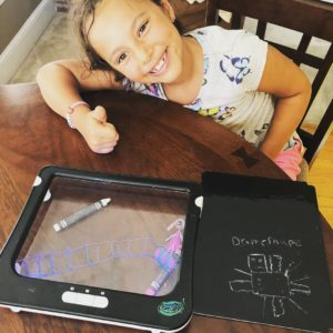 photo of girl leaning over tablet with drawing of hero on it